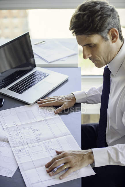 Man working with blueprints in the office — Stock Photo