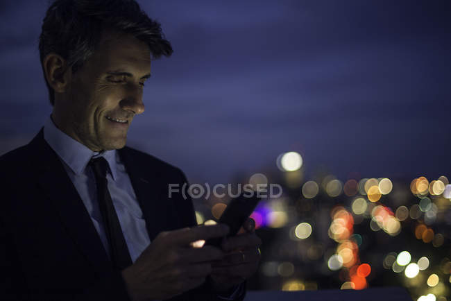 Empresário no telhado de arranha-céus usando telefone celular — Fotografia de Stock