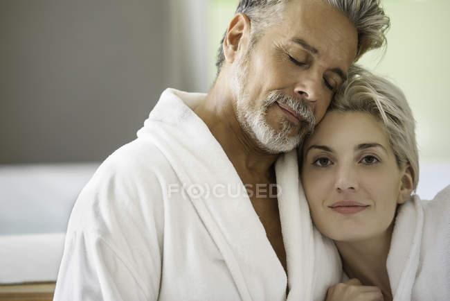 Пара в халатах, обнимающихся в спа — стоковое фото