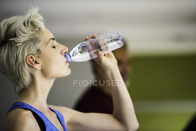 Femme boire de l'eau de bouteille tout en faisant de l'exercice sur tapis roulant — Photo de stock
