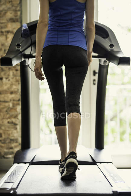 Back view of Woman exercising on treadmill — Stock Photo