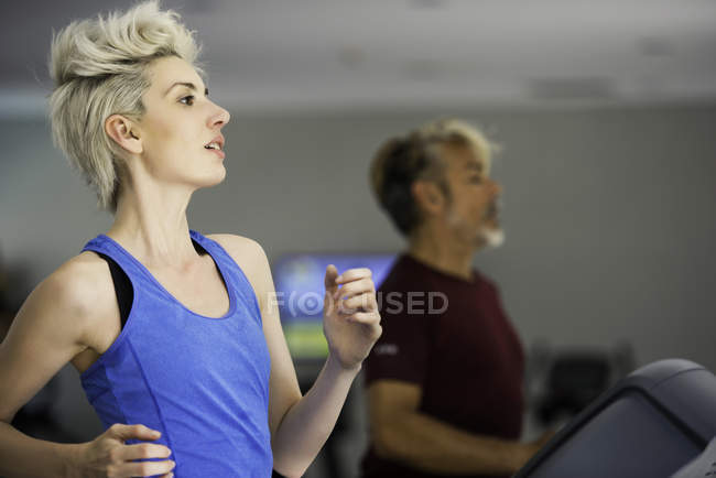Woman and man exercising on treadmills — Stock Photo