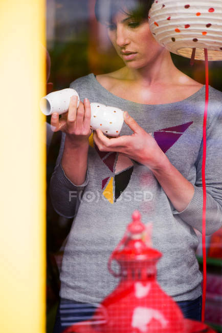 Woman shopping decorations for home, viewed through window — Stock Photo