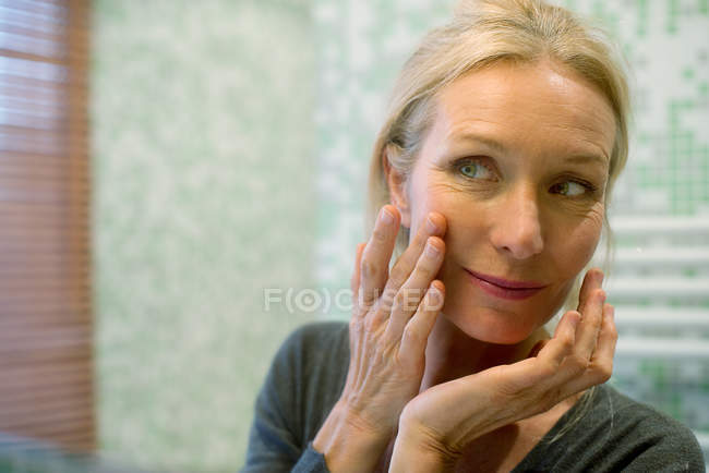 Mature woman looking at reflection in mirror with hand on cheek — Stock Photo