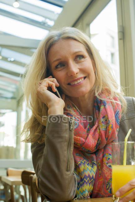 Femme mûre parlant sur un téléphone portable et souriant dans un café — Photo de stock