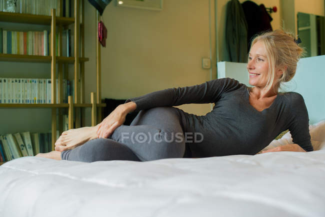 Mature woman relaxing on bed — Stock Photo
