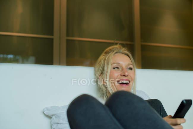 Femme d'âge mûr rire en regardant la télévision — Photo de stock