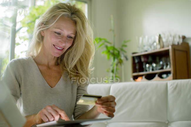 Reife Frau mit digitalen Tisch online Shop — Stockfoto