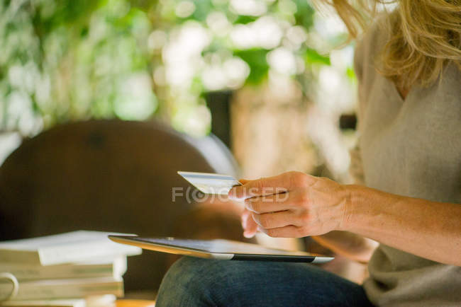 Woman using digital tablet and credit card, cropped shot — Stock Photo