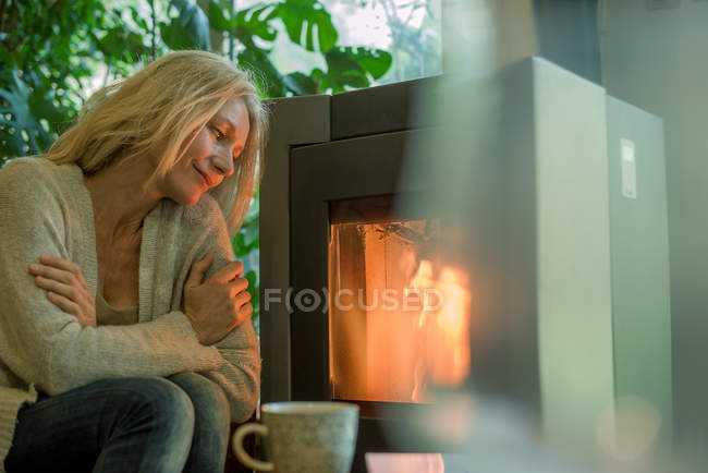 Mature woman relaxing by fireplace — 45-49 years, view