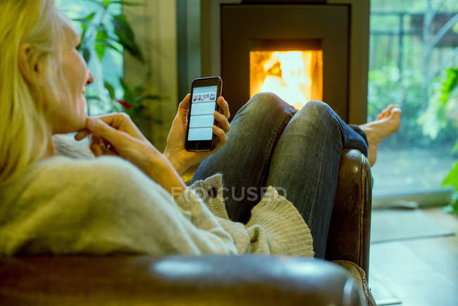 Mulher madura em casa relaxando com smartphone — Fotografia de Stock