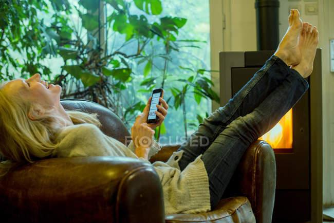 Mulher madura, rindo enquanto relaxa em casa com smartphone — Fotografia de Stock
