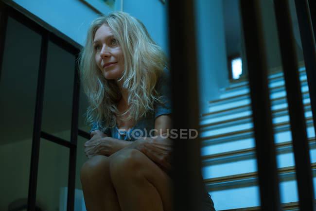 Reife Frau sitzt auf der Treppe und schaut gedankenverloren weg — Stockfoto