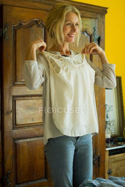 Donna matura in piedi in camera da letto, tenendo la camicetta contro il petto e sorridendo — Foto stock