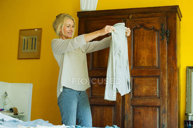 Mature woman standing in bedroom, holding out shirt — Stock Photo