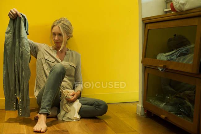 Зрелая женщина, сидящая на полу в спальне, созерцая рубашку — стоковое фото
