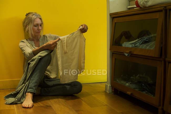 Зрелая женщина сидит на полу и смотрит на рубашку с несчастливым выражением лица — стоковое фото