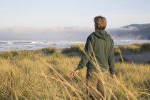 Man walks through tall grasses in dunes — Stock Photo