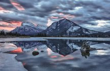 Mountains and cloudy sky reflected in  lake — Stock Photo