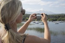 Woman taking photos of boats in marina — Stock Photo