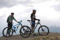 Männer stehen mit Fahrrädern auf Berg — Stockfoto