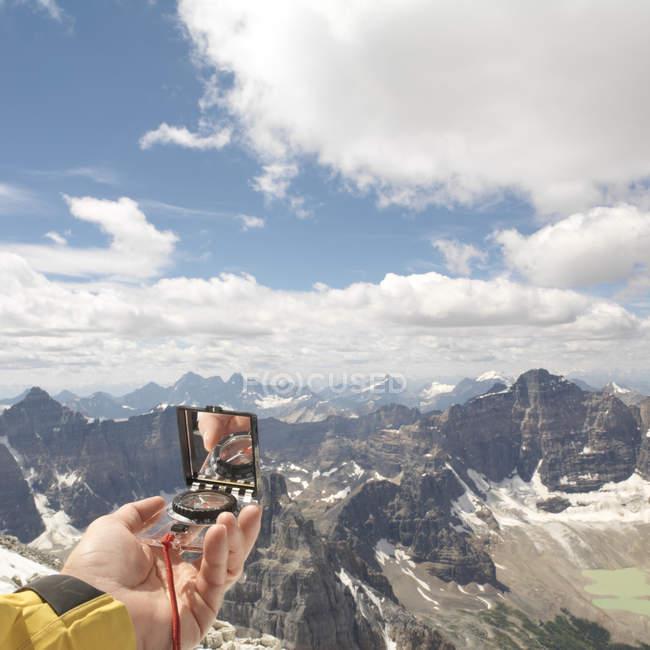 Bussola della holding della mano sopra le montagne — Foto stock