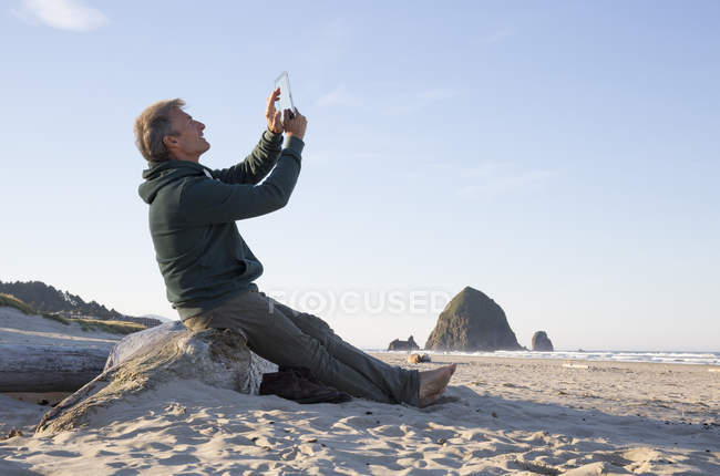Man sits on beach log and uses tablet — Stock Photo