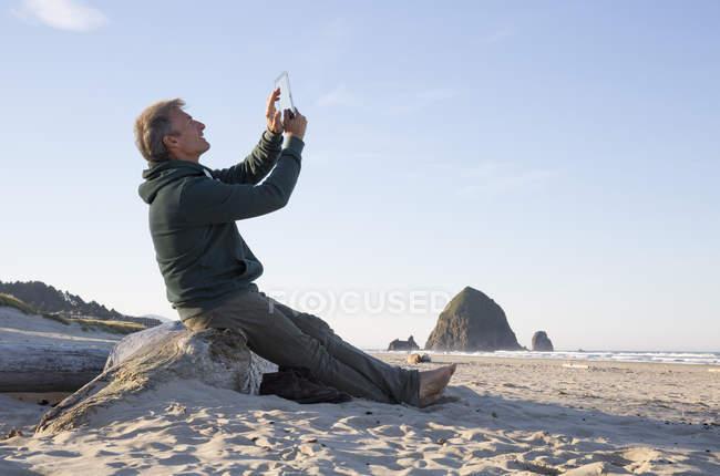 Mann sitzt am Strand Log und tablet — Stockfoto