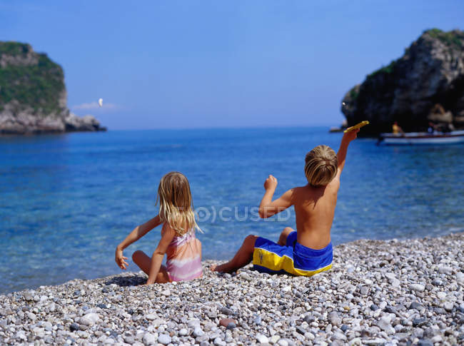 Boy and girl throwing rocks — Stock Photo