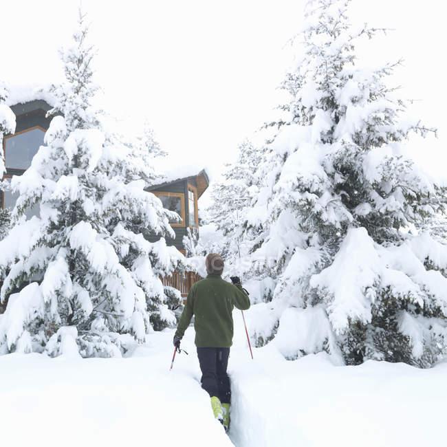 Человек, Катание на лыжах в Альпийский дом — стоковое фото