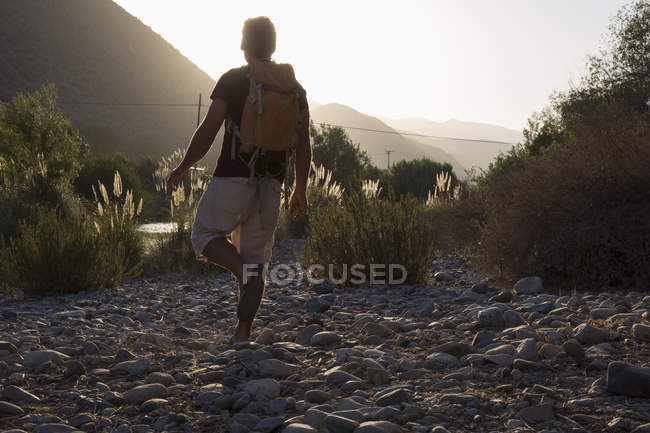 Hiker walking along riverbank — Stock Photo