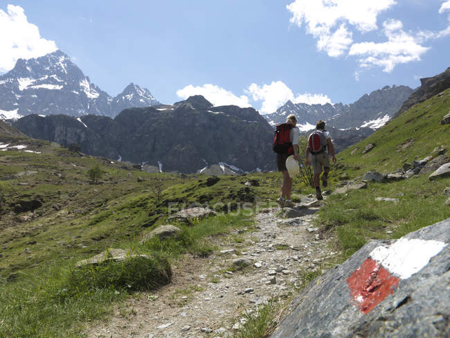 Hikers walking in mountains — Stock Photo