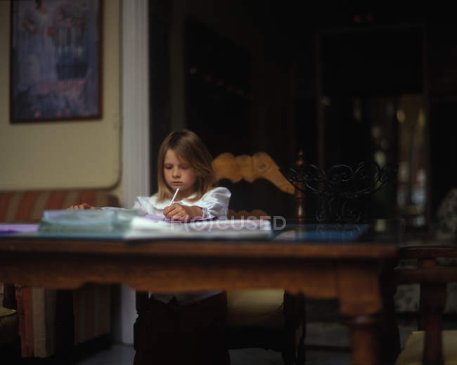 Young girl sitting at antique table and doing homework — Stock Photo
