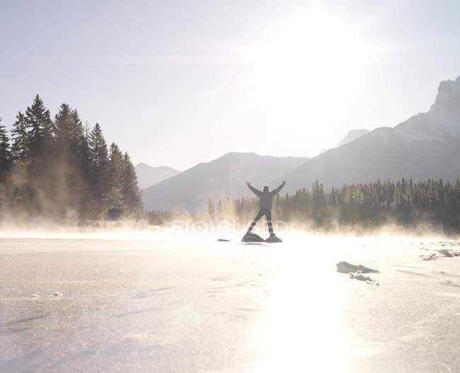 Homem de pé sobre rochas em lago congelado — Fotografia de Stock
