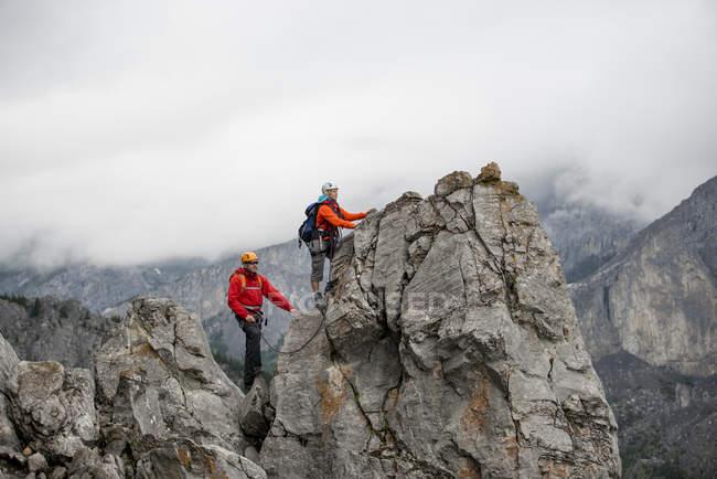 People climbing on rock in mountains — Stock Photo