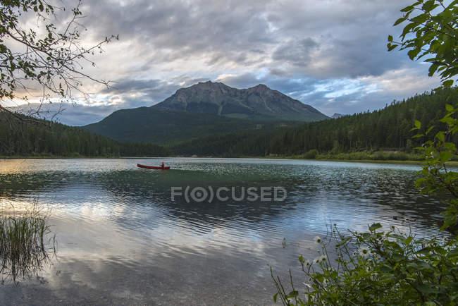 Лодка, плавающая в горное озеро — стоковое фото