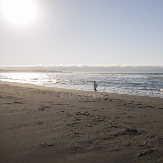 Зріла людина, що біжить на піщаному пляжі — стокове фото