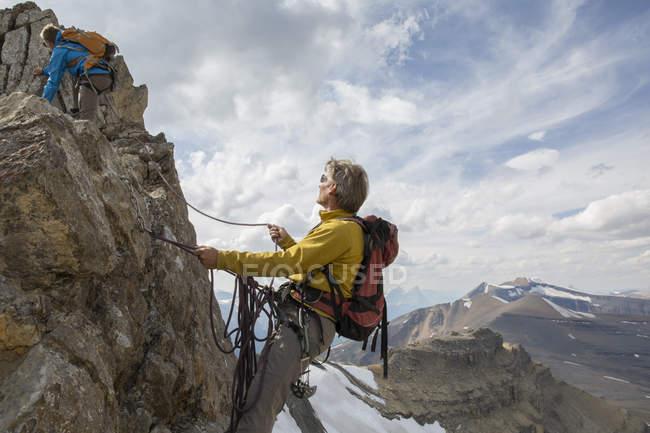 Adultos escaladores en roca en las montañas - foto de stock
