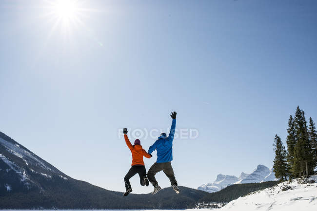Couple jumping in mountains and blue sky — Stock Photo