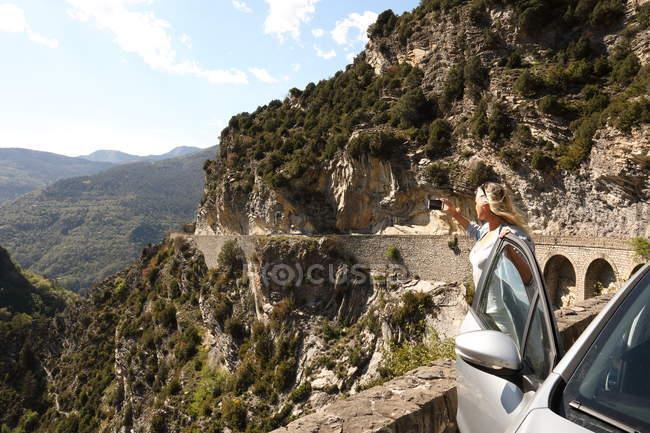 Woman taking photos on mountain road — Stock Photo