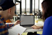 Hombre y mujer a la mesa del ordenador portátil - foto de stock