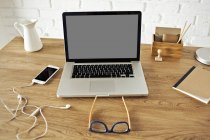 Laptop y smartphone en mesa de madera - foto de stock