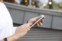 Mani femminili che tengono smartphone — Foto stock