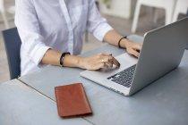 Manos escribiendo en el teclado del ordenador portátil - foto de stock