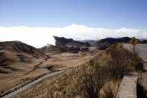 Deserted landscape by the roadwith clouds on mountains in sunny daytime, Argentina — Stock Photo
