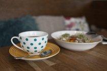 Gepunktete Tasse Tee und Schüssel mit Salat — Stockfoto