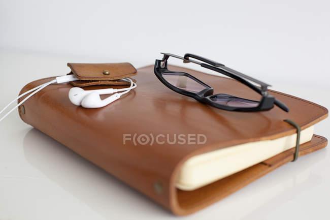 Leder Notebook mit Brille und Kopfhörer — Stockfoto