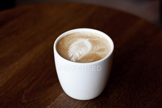 Cup of fresh made coffee on wooden table — Stock Photo