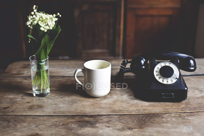 Кубок, телефоном та bouqette травня лілії — стокове фото