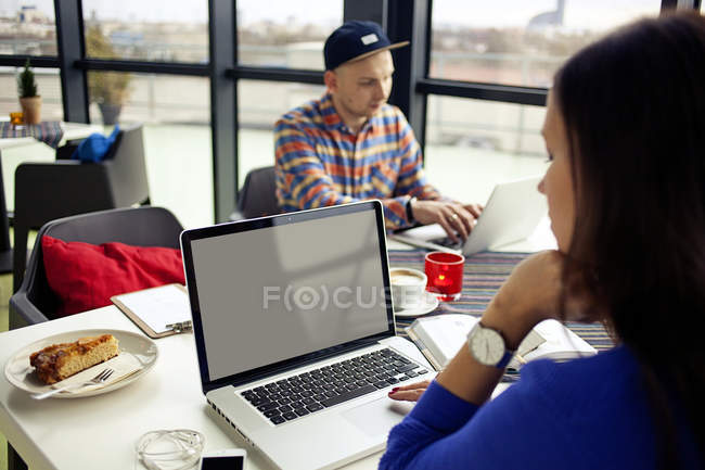 Man and woman at table with laptops — Stock Photo